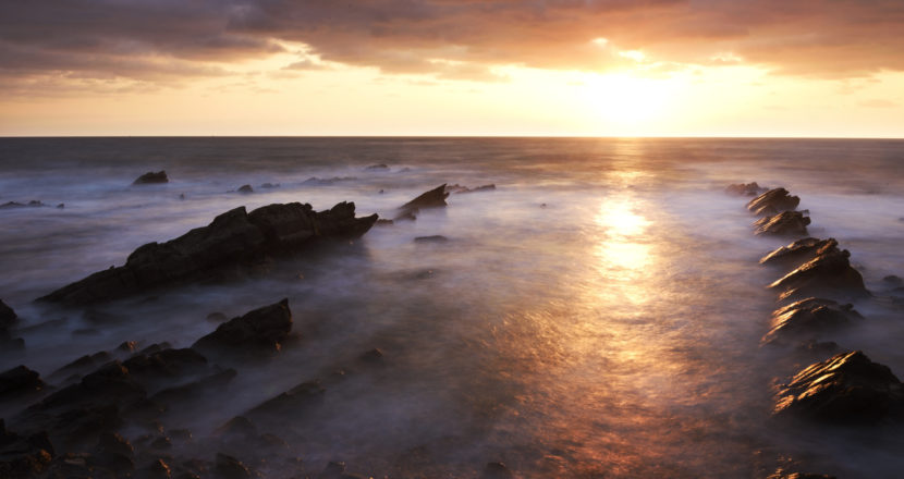 Sunrise with stormy clouds on the rocky coast